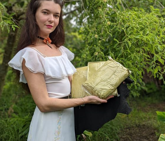 Jamie holding kratom powder in front of kratom tree
